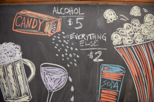 photo of chalkboard showing pricing, candy,beer, wine, soda, and popcorn.
